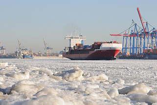 02_5775 Zwei Frachtschiffe verlassen im dichten Eis der Elbe den Hamburger Hafen - rechts die Container - Br�cken am HHLA Terminal Burchardkai. Im Vordergrund ist der Elbstrand von �velg�nne mit Eisschollen bedeckt
