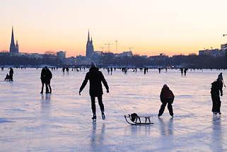 58_5942 Die zugefrorene Alster bedeutet für die Hamburger ein Volksfest. Bis in den späten Abend wird auf dem Alstereis Schlittschuh gelaufen oder geschlendert. Fotos vom winterlichen Hamburg - Schlitten fahren und Schlittschuh laufen auf der abendlichen