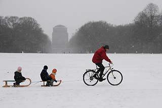 64_5069 Der Hamburger Stadtpark ist eingeschneit. Ein Vater zieht mit seinem Fahrrad die zwei Schlitten seiner Kinder durch den Schnee �ber die gro�e Wiese. Bilder vom Winter in der Hansestadt Hamburg - Winterfreuden im Hamburger Stadtpark.